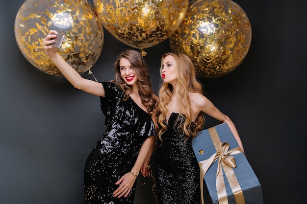 Happy party moments of two fashionable young women making selfie. luxury black dress, long curly hair, big balloons with golden tinsels, present, having fun, smiling. Free Photo