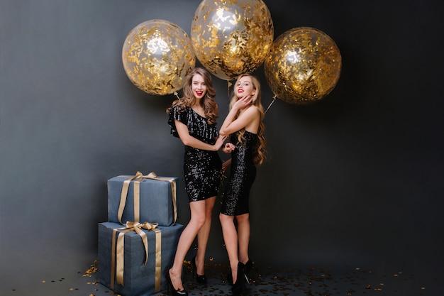 豪華な黒のドレスを着た2人の魅力的な若い女性の幸せなパーティータイム。長い巻き毛、魅力的な外観、プレゼント、金色の見掛け倒しの大きな風船、笑顔、楽しんでいます。 無料写真