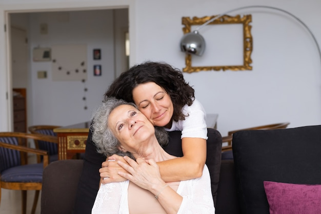 Happy peaceful middle aged woman hugging elderly lady Free Photo