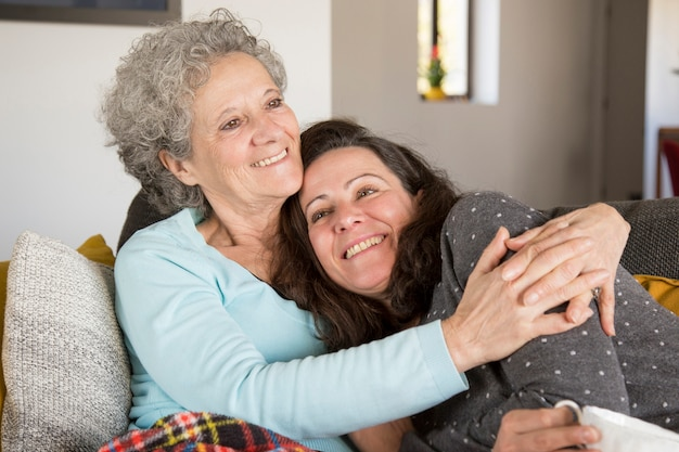 Happy pensive senior lady embracing her daughter at home Free Photo