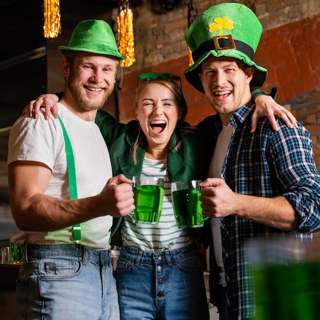 聖を祝う幸せな人々。飲み物を飲みながらバーでパトリックの日 無料写真