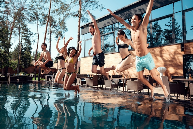 Happy people having fun by jumping from poolside into water. Premium Photo