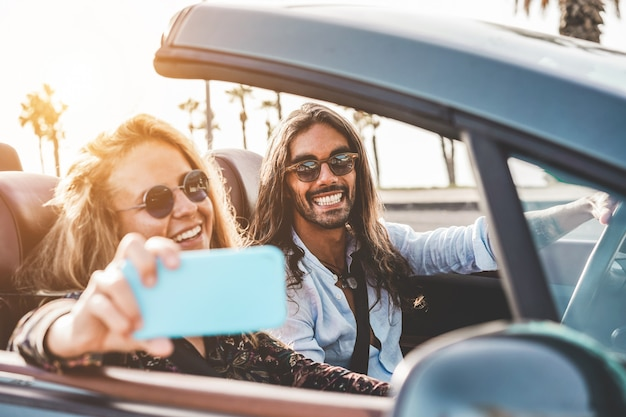 Happy people having fun in convertible car making videos for social network - young couple enjoyng holiday on cabriolet outdoor - travel, youth lifestyle and wanderlust concept - focus on man face Premium Photo