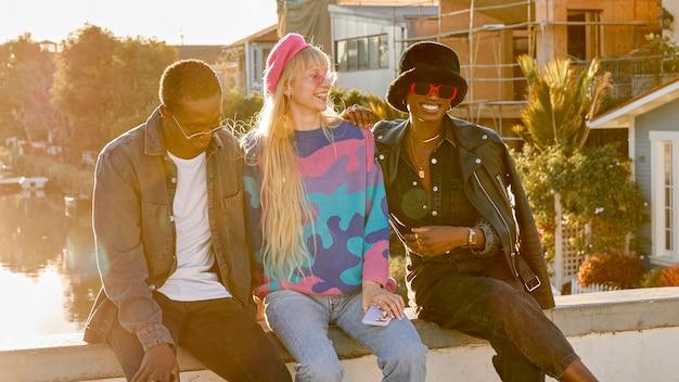 Счастливые люди сидят вместе на открытом воздухе Бесплатные Фотографии