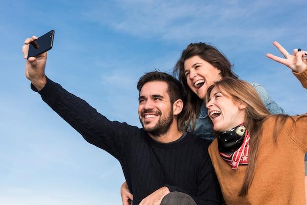 Happy people taking selfie on blue sky background Free Photo