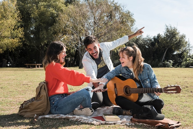 Happy people with guitar on coverlet Free Photo