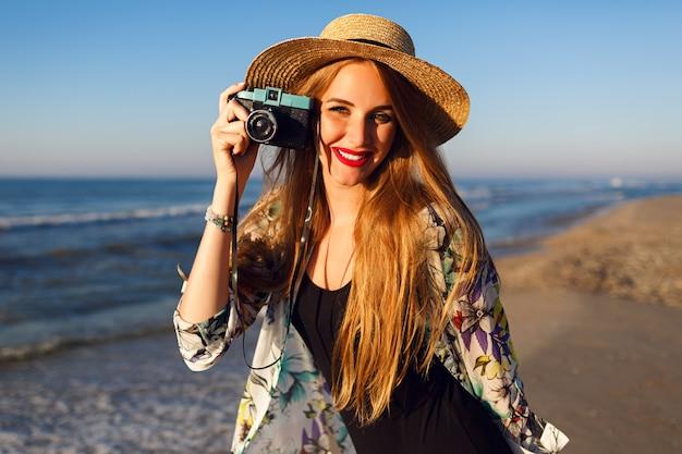 Счастливая мелкая женщина с длинными светлыми волосами веселится и фотографирует на пляже у океана на старинную камеру, солнечные цвета Бесплатные Фотографии