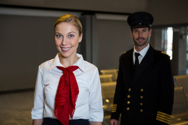 Happy pilot and air hostess standing in the airport terminal Free Photo