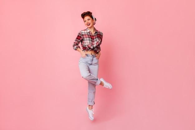 주머니에 손을 포즈 행복 핀 업 소녀. 분홍색 공간에 서있는 체크 무늬 셔츠에 생강 여자를 웃 고있다. 무료 사진