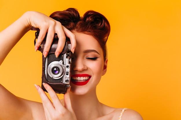 写真を撮る幸せなピンナップガール。黄色の空間に分離されたカメラを持つ女性のスタジオポートレート。 無料写真