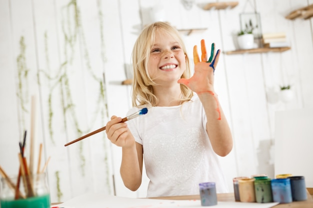 Happy and playful cute freckled blonde girl dressed in white, holding brush in one hand and showing another hand, which she messed up with paint. Free Photo