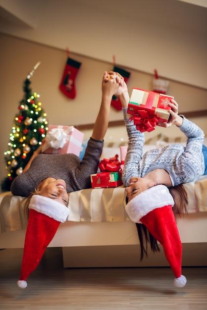 Счастливые игривые милые рождественские друзья с санта шляпы и свитера, наслаждаясь дома на праздники. Premium Фотографии