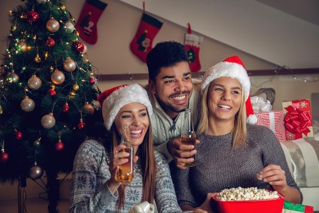 Счастливые игривые милые рождественские друзья со шляпами санты Premium Фотографии