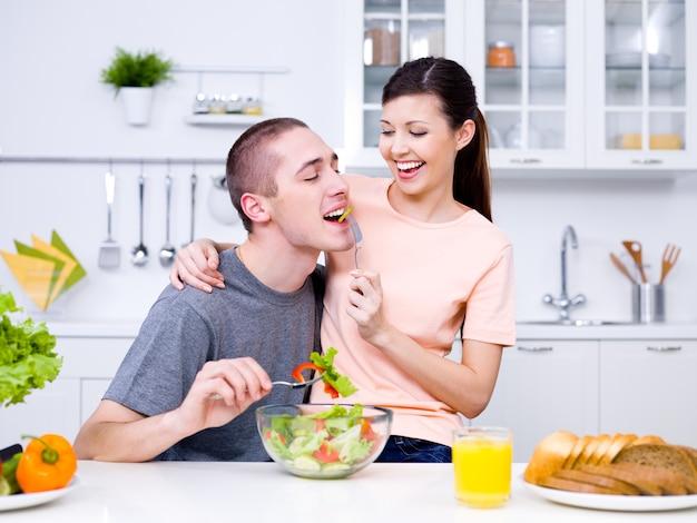 Giovani coppie allegre felici che mangiano insieme nella cucina Foto Gratuite