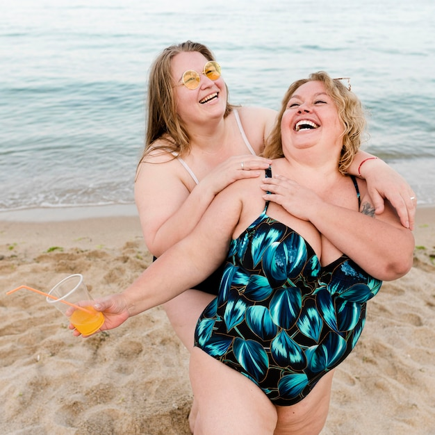 Happy plus size friends at the beach Free Photo