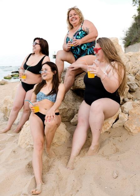 一緒に岩の上に座って幸せなプラスのサイズの友達 無料写真
