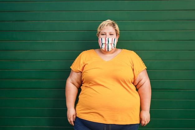 코로나 바이러스 발생 동안 얼굴 보호 마스크를 쓰고 행복 더하기 크기 여자 프리미엄 사진