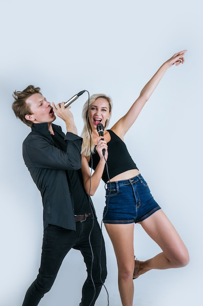 Happy portrait of couple holding microphone and sing a song Free Photo