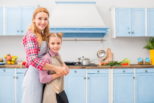 Happy portrait of mother and daughter looking at camera standing in the kitchen Free Photo