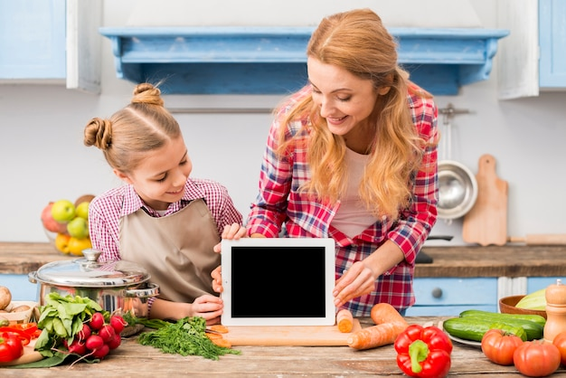 Happy portrait of mother and daughter looking at digital tablet on wooden desk Free Photo