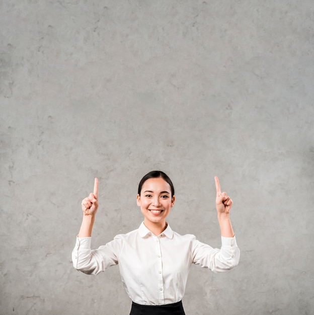 Happy portrait of a smiling young businesswoman pointing her fingers upward against grey wall Free Photo