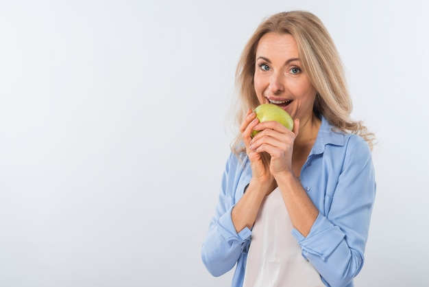 Happy portrait of a smiling young woman eating green apple against white background Free Photo