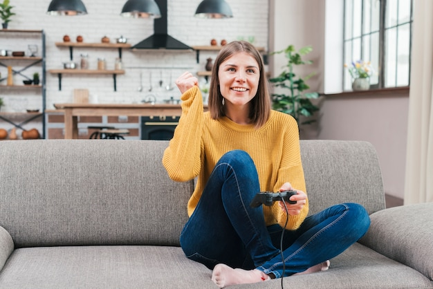 Happy portrait of a smiling young woman sitting on sofa playing the video game Free Photo
