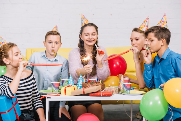 Happy portrait of a teenage girl holding firecracker in hand enjoying in the birthday party Free Photo