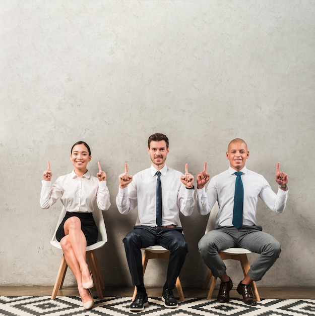 Happy portrait of a young businessman and businesswoman sitting on chair pointing their fingers upward Free Photo