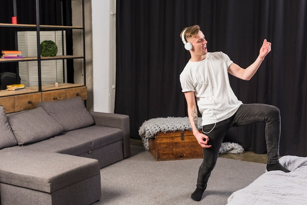 Happy portrait of a young man playing an invisible guitar with headphone on his head Free Photo