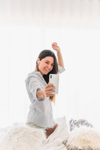 Happy portrait of a young woman taking selfie on smartphone Free Photo