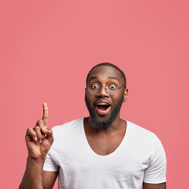 Happy positive african american male adult has dark skin and thick beard Free Photo