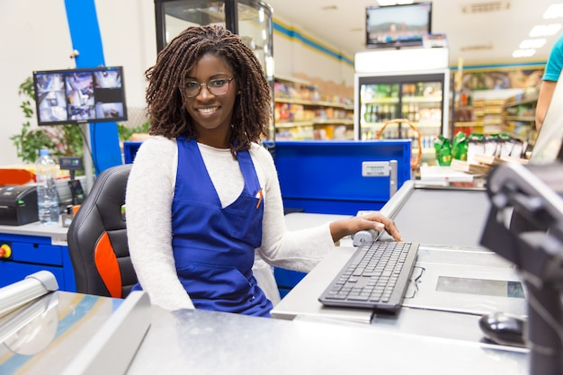 Happy positive female cashier working in grocery store Free Photo