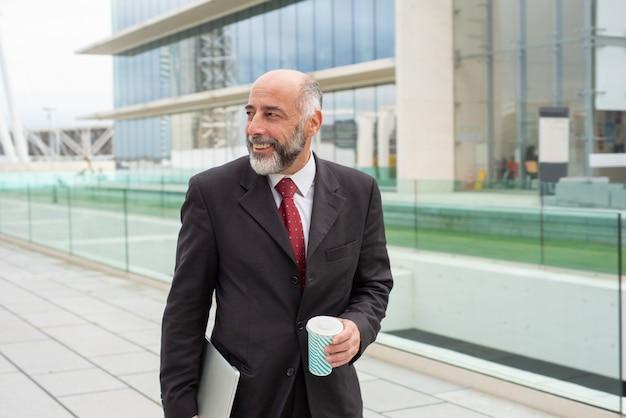 Happy positive mature business leader enjoying coffee Free Photo