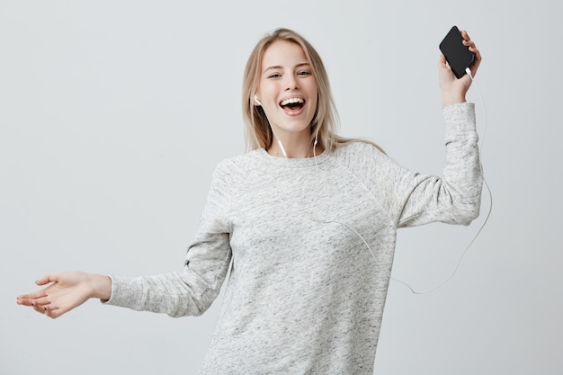 Счастливая позитивная женщина танцует в радости, держит мобильный телефон, широко улыбается, слушает любимые песни в белых наушниках, использует музыку Бесплатные Фотографии