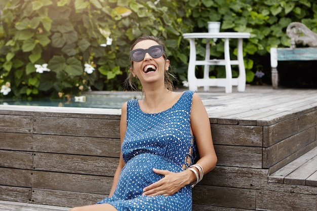 幸せな妊娠と出産の概念。新鮮な空気と外の暖かい天候を楽しんでいるサングラスをかけている若い妊娠中の女性、木の床のプールに座って、元気に笑っています。 無料写真