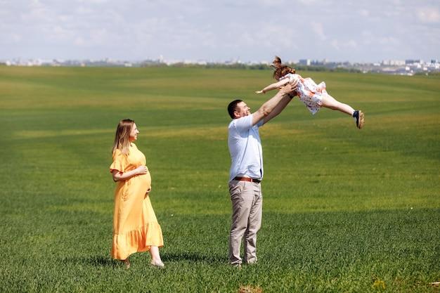 夏の日に日当たりの良い緑のフィールドで一緒に時間を過ごす小さな娘と一緒に幸せな妊娠中の家族 Premium写真