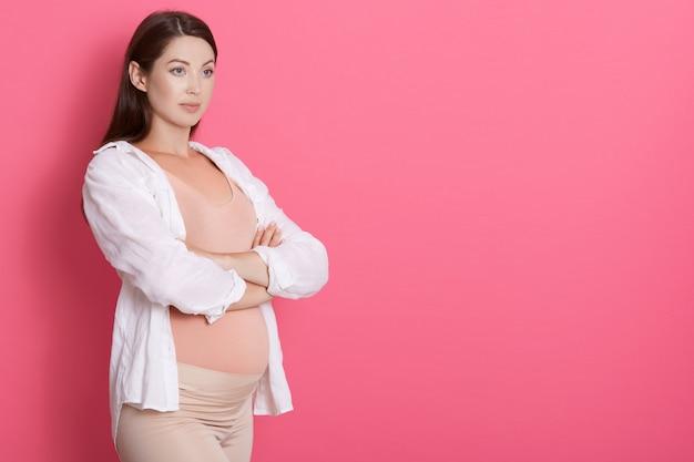 Felice signora incinta in piedi con le braccia incrociate e guardando da parte, ha uno sguardo serio Foto Gratuite