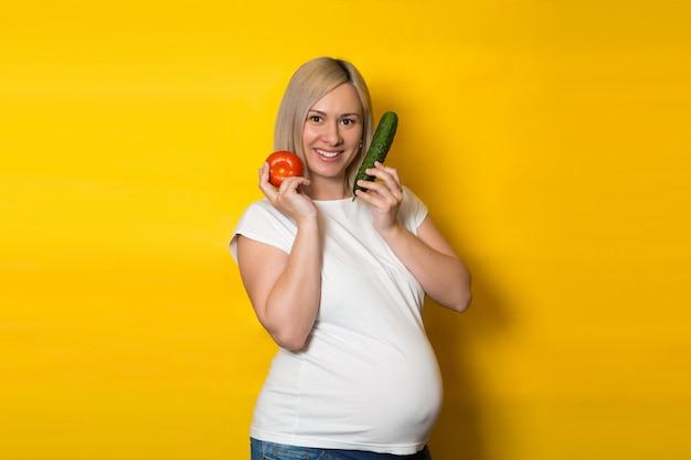 Счастливая беременная женщина выбирает между пилюльками и овощами на желтой стене. питание и диета во время беременности Premium Фотографии