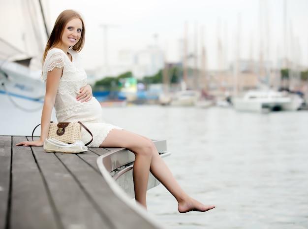 Happy pregnant  woman in sea port Free Photo