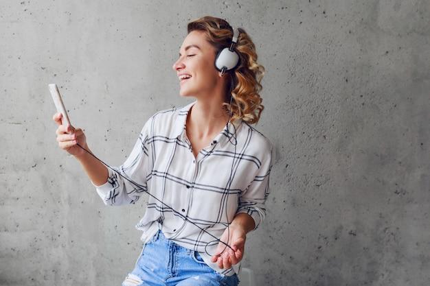 灰色の都市壁の背景に椅子に座って、イヤホンで音楽を楽しんで幸せなかなり金髪流行に敏感な女性。 無料写真