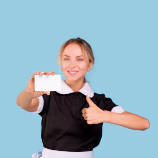 空白の名刺と親指ジェスチャーを示す幸せなきれいな女性用務員 無料写真