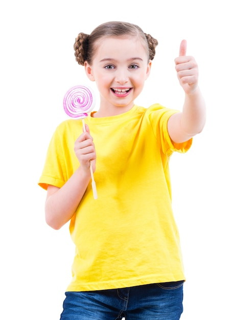 親指を立てるサインを示す色付きのキャンディーと黄色のtシャツの幸せなかわいい女の子-白で隔離。 無料写真