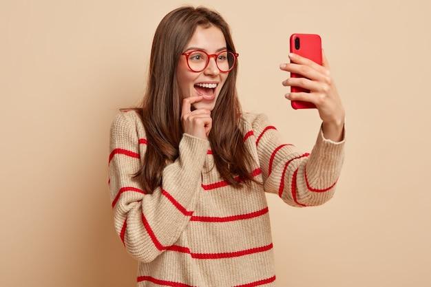 Счастливая симпатичная девушка делает забавные фото, нажимает на селфи на современном мобильном телефоне, публикует сообщения в соцсети, любит фотографировать себя, носит прозрачные очки, носит повседневный джемпер, изолирована Бесплатные Фотографии