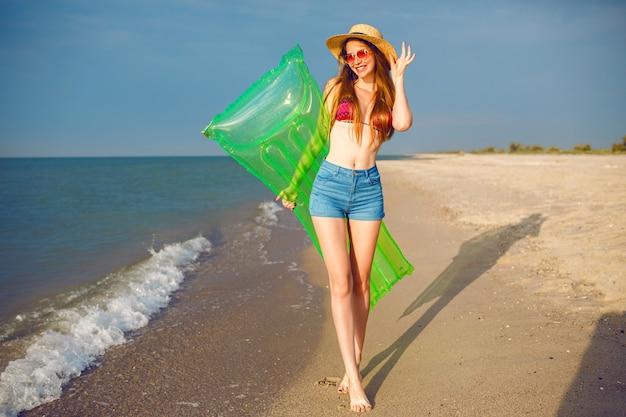 Счастливая симпатичная женщина веселится на пляже, одетая в стильную пляжную одежду, бикини и джинсовые шорты, с длинными ногами, стройным телом, держит надувной матрас и гуляет возле океана. Бесплатные Фотографии