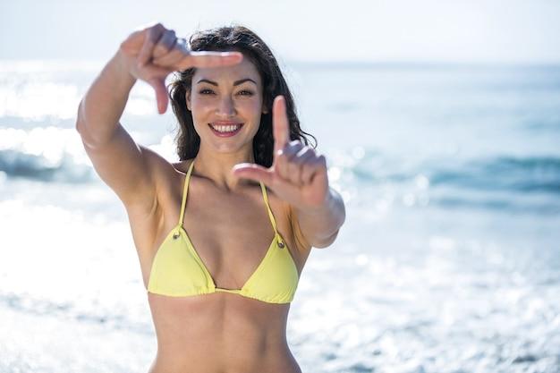 Счастливая красивая женщина в бикини, делая кадр пальца Premium Фотографии