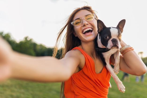 自撮り写真を作る幸せなきれいな女性公園、ボストンテリア犬を抱いて、ポジティブな気分を笑顔、トレンディな夏のスタイル、オレンジ色のドレス、サングラスを身に着けて、ペットと遊んで、楽しんでください 無料写真