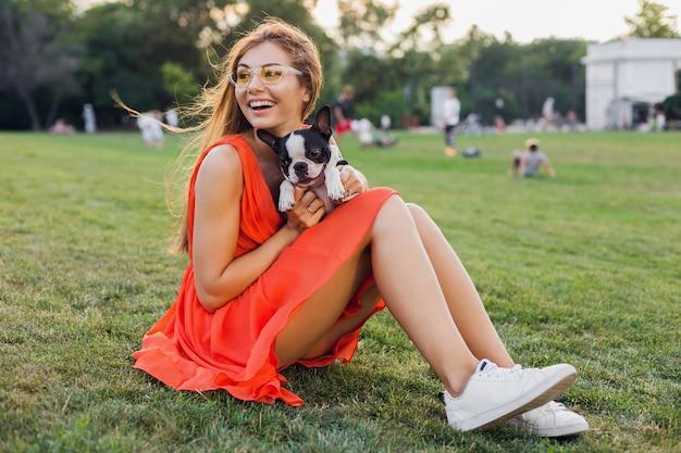 Felice bella donna seduta sull'erba nel parco estivo, tenendo in mano il cane boston terrier, sorridente stato d'animo positivo, indossando un abito arancione, stile alla moda, gambe snelle, scarpe da ginnastica, giocando con animali da compagnia, intrattenimento di fine settimana Foto Gratuite