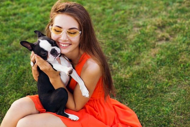 夏の公園の芝生に座って、ボストンテリア犬を抱いて、キス、オレンジ色のドレスを着て、流行のスタイル、ペットと遊ぶ幸せなきれいな女性 無料写真