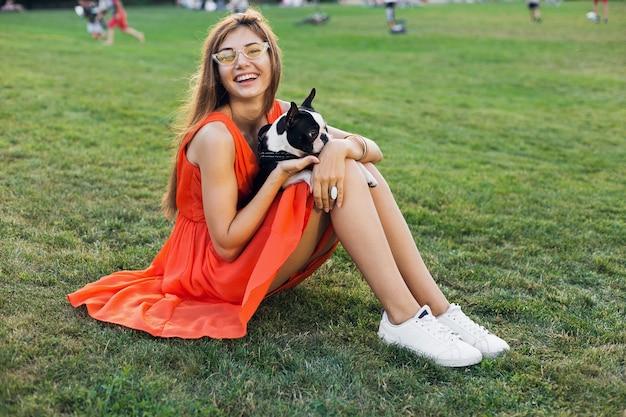 Счастливая симпатичная женщина, сидящая на траве в летнем парке, держа собаку бостон-терьера, улыбаясь позитивным настроением, в оранжевом платье, в модном стиле, стройные ноги, кроссовки, играя с домашним животным Бесплатные Фотографии
